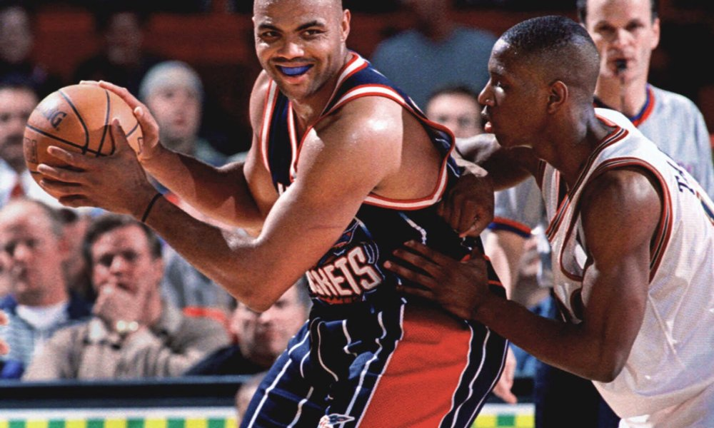 FILE -- Houston Rockets forward Charles Barkley smiles to expose his mouthpiece as he backs into Denver Nuggets forward Johnny Taylor in the fourth period of the Rockets' 114-109 victory in Denver's McNichols Sports Arena Wednesday, March 17, 1999. Barkley has threatened several times in recent years to retire. This time, the 36-year-old forward insists, he means it.     Barkley said Friday Oct. 22, 1999 he will announce his retirement, effective at season's end, at halftime of the Houston Rockets' exhibition game with the Detroit Pistons on Sunday at Birmingham, Ala. (AP Photo/David Zalubowski) ORG XMIT: NY153